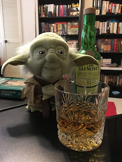 A whisky tumbler with a double measure of The Glenlivet 12-Year-Old sits on a desk before a half-size bottle of same and a stuffed Yoda keeps watch. Background: Bookcases.