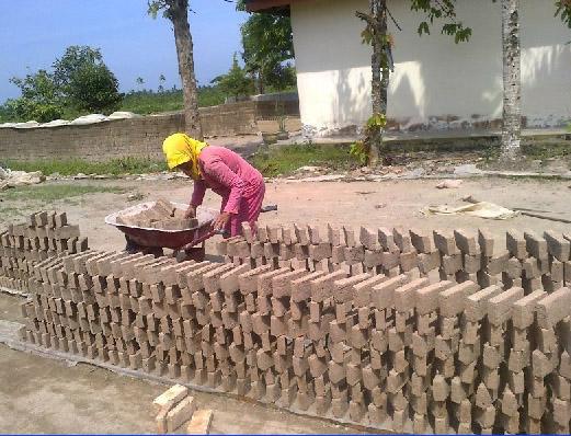 Perajin batu bata sedang menjemur batu bata yang baru selesai dicetak.