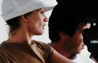 La cineasta, en primer plano de perfil, con camiseta y sombrero, rodando una película.