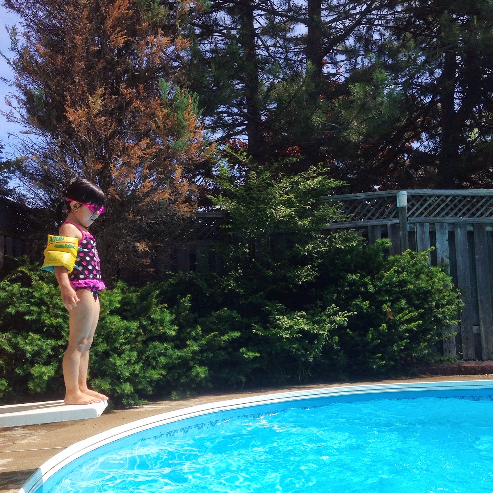 girl jumping diving board swimming pool summer