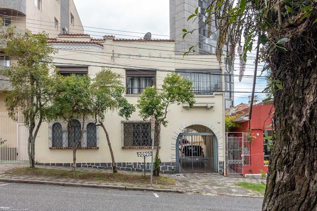 Casa com janelas em arco, colunas espiraladas e platibanda