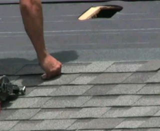 Man with a nail gun on roof top