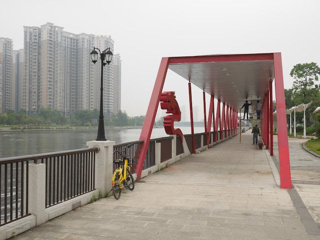 men painting a riverside covered walkway sculpture at the Dragon Boat Cultural Park (龙舟文化公园)
