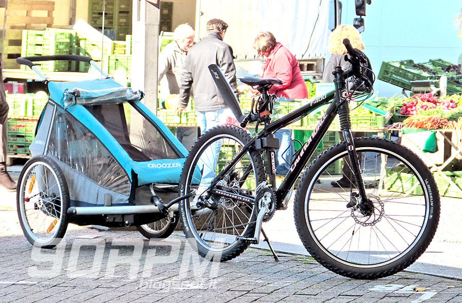 Una bicicletta traina un carrellino per il trasporto dei bambini