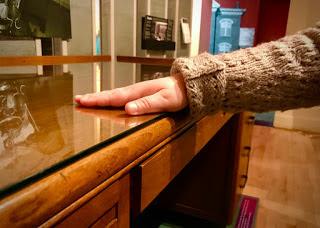 Ant medinio stalo viršaus uždėtas stiklas, kurį lankytoja liečia ranka.