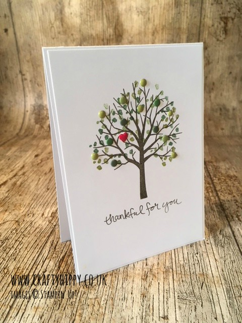 A picture of a greetings card depicting a tree made with the Sheltering Tree stamp set by Stampin' Up! It has green leaves and a red heart.