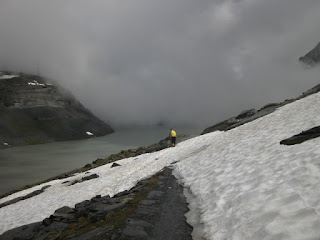 Cyclist traversing snowfield along the Gemmipass, Switzerland
