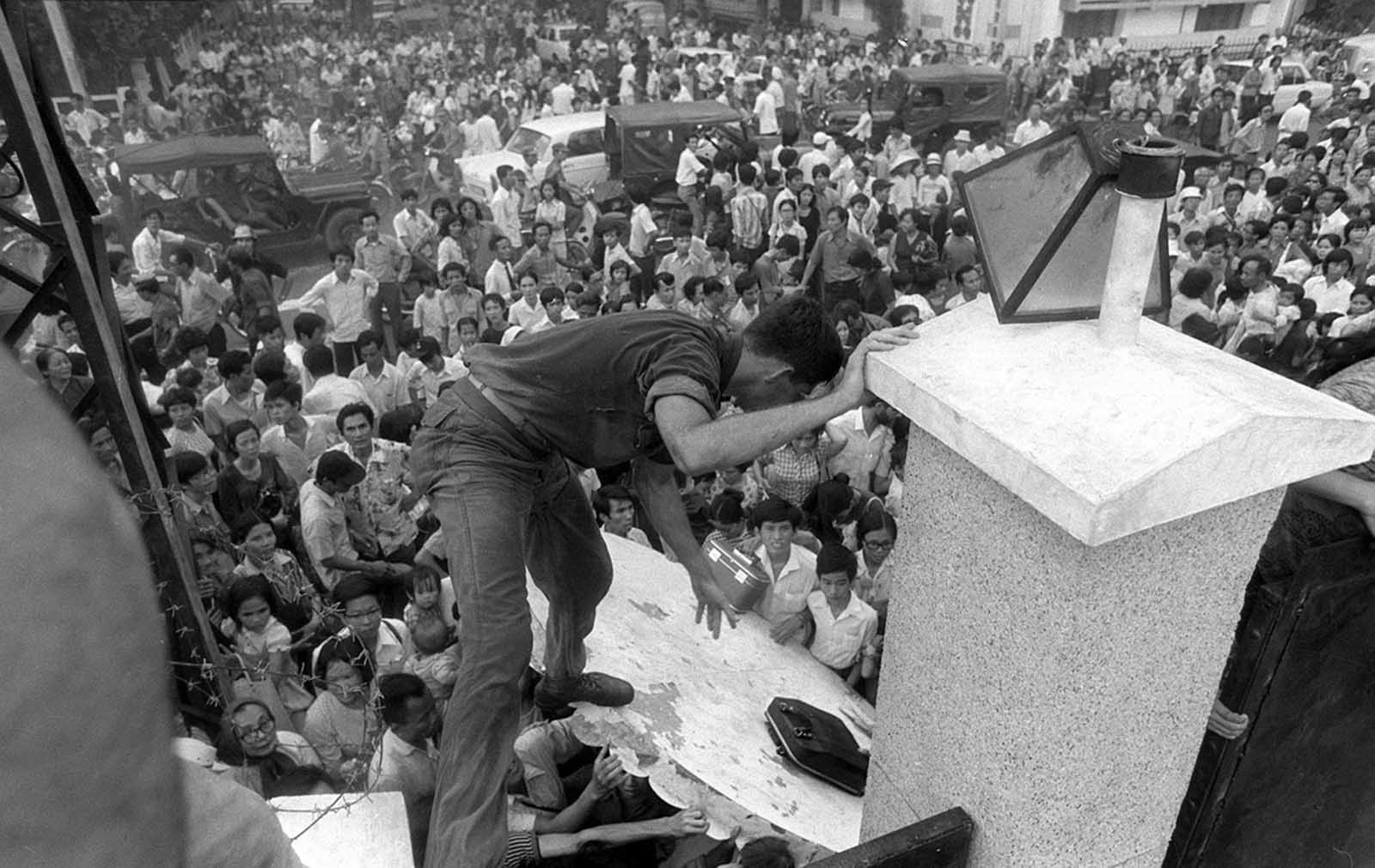 The Fall of Saigon. Fleeing advancing North Vietnamese forces, mobs of South Vietnamese civilians scale the 14-foot wall of the U.S. embassy in Saigon, April 29, 1975, trying to reach evacuation helicopters as the last Americans departed from Vietnam.