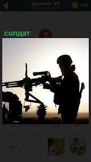 Силуэт солдата в каске и форме, держащий пулемет с прицелом