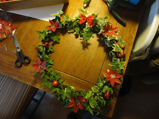 Ivy wreath with red bow, baubles and poinsettia