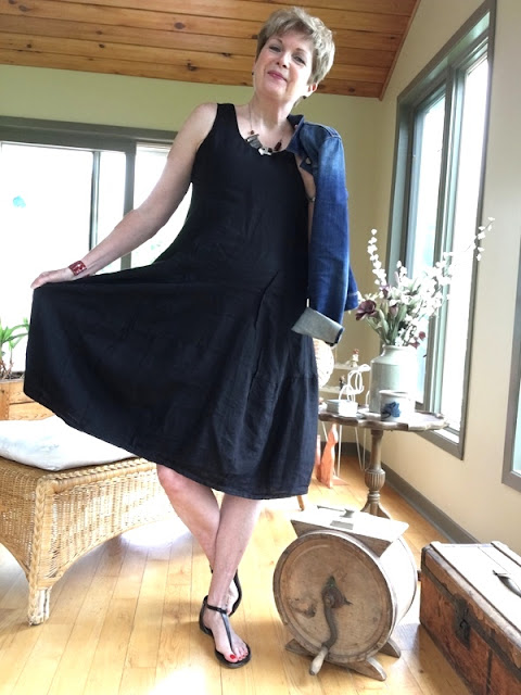 woman in black dress and sandals holding a denim jacket