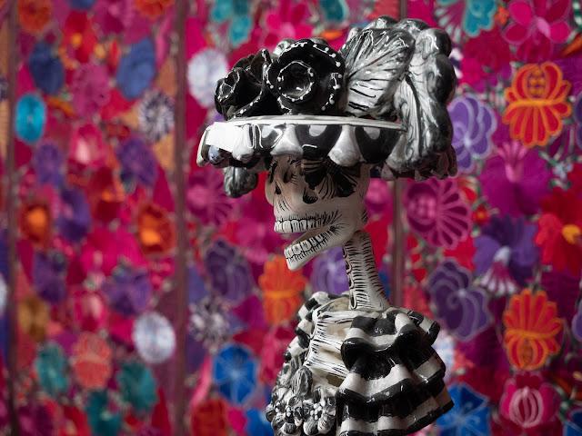 Esqueleto mejicano sobre un colorido tapiz fucsia de fondo