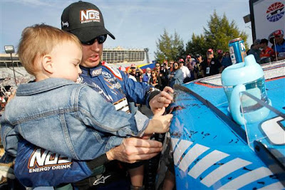 Kyle Busch and his son Brexton affix the winner's decal to his car in  Victory Lane.
