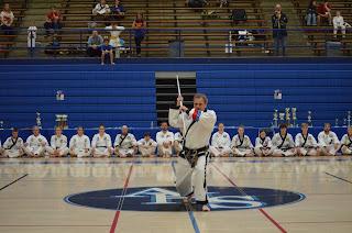 A taekwondo master black belt performing staff pattern in demonstration