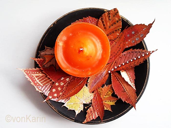 Herbstdeko, bemalte Baumblätter und Kerze in Orange auf schwarzem Teller