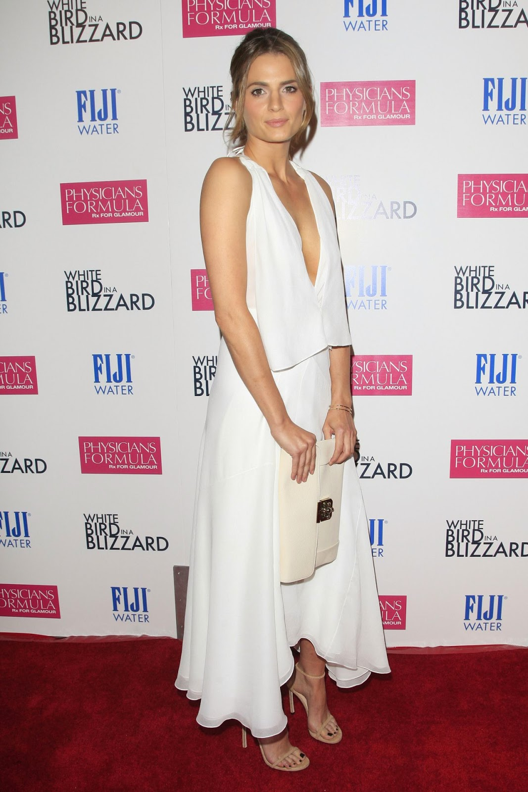 Stana Katic in a plunging white top and skirt at the 'White Bird in a Blizzard' LA premiere