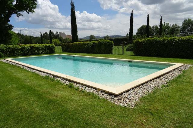 Pool umgeben von grünem Rasen mit Blick auf Zedern, Himmel blau und Wolken