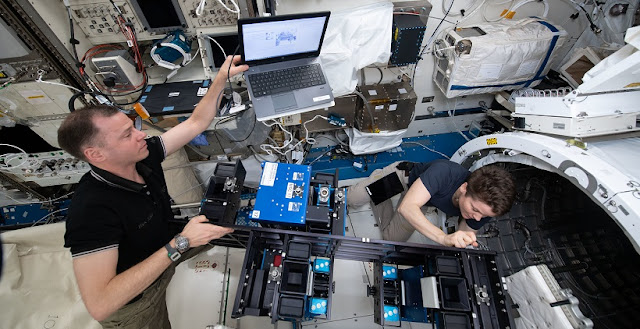 NASA astronauts Nick Hague and Anne McClain install the Materials ISS Experiment-Flight Facility (MISSE-FF) gear inside the Japanese Kibo laboratory module's airlock before depressurizing the unit. Credit: NASA