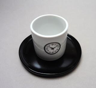 tasse et sous-tasse noir et blanc avec motif horloge