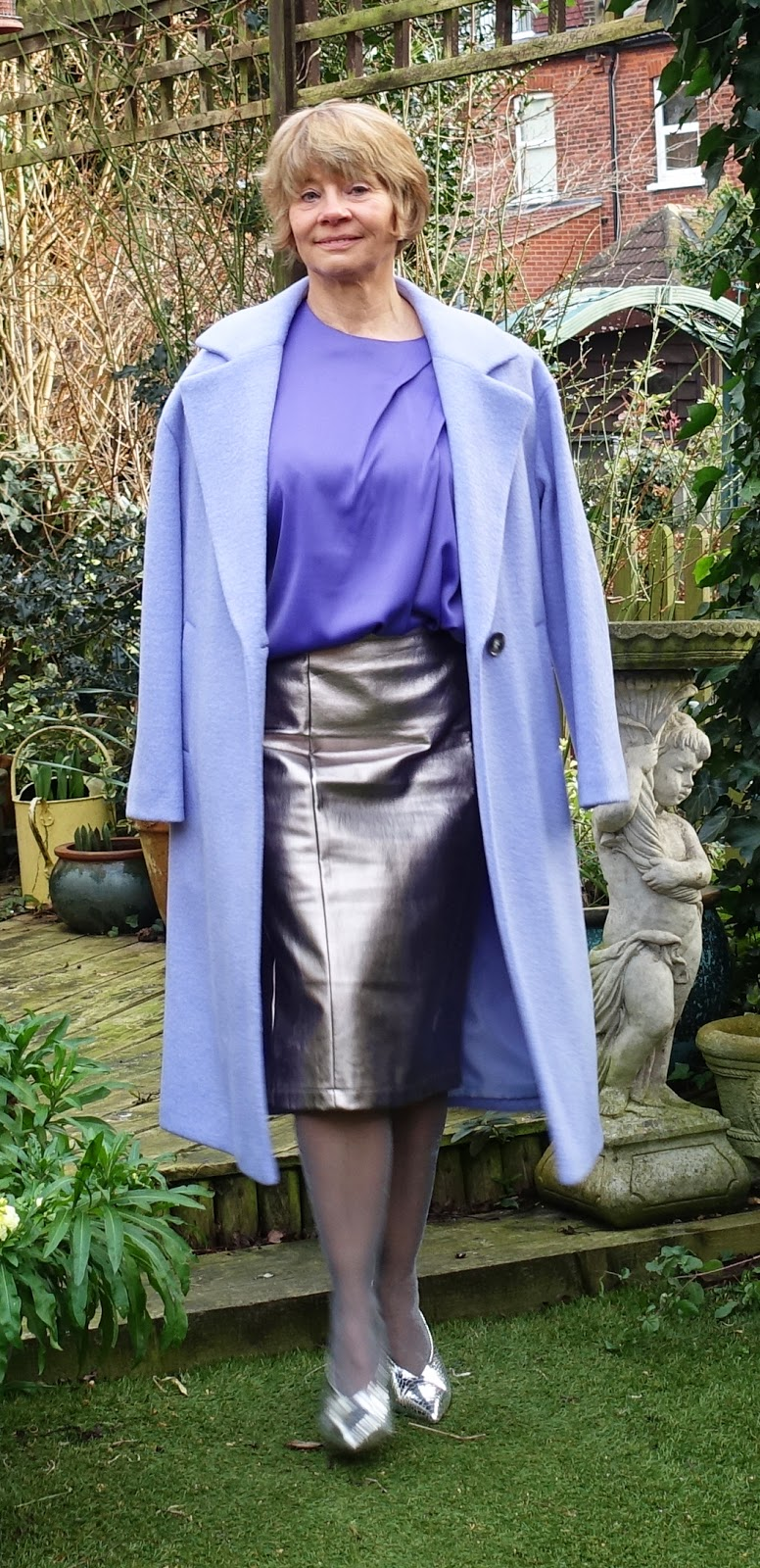 Image showing a garden shot of an over 45 woman in lilac wool coat, silver pleather pencil skirt and purple draped shell top.