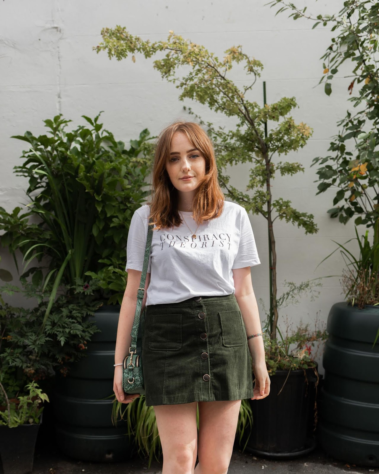 blogger wearing 'conspiracy theorist' white t-shirt and green corduroy button up mini skirt