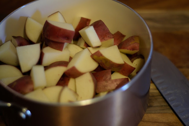 The diced red potatoes in a pot with a knife to the right of it.