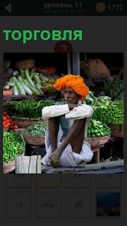 Продавец на рынке осуществляет торговлю в позе йога с желтым национальном головном уборе и одежде