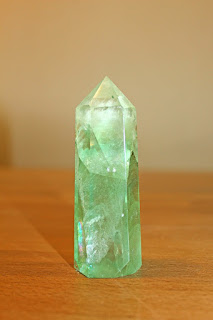 A translucent, pale green crystal with a flat bottom rests on a wooden surface. The colour is deeper at the base and gets lighter as you get closer to the pointed tip.