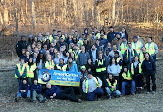 A group of AmeriCorps members stand together holding an AmeriCorps banner.