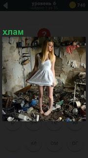 Девушка в белом платье стоит среди хлама в помещении грязном