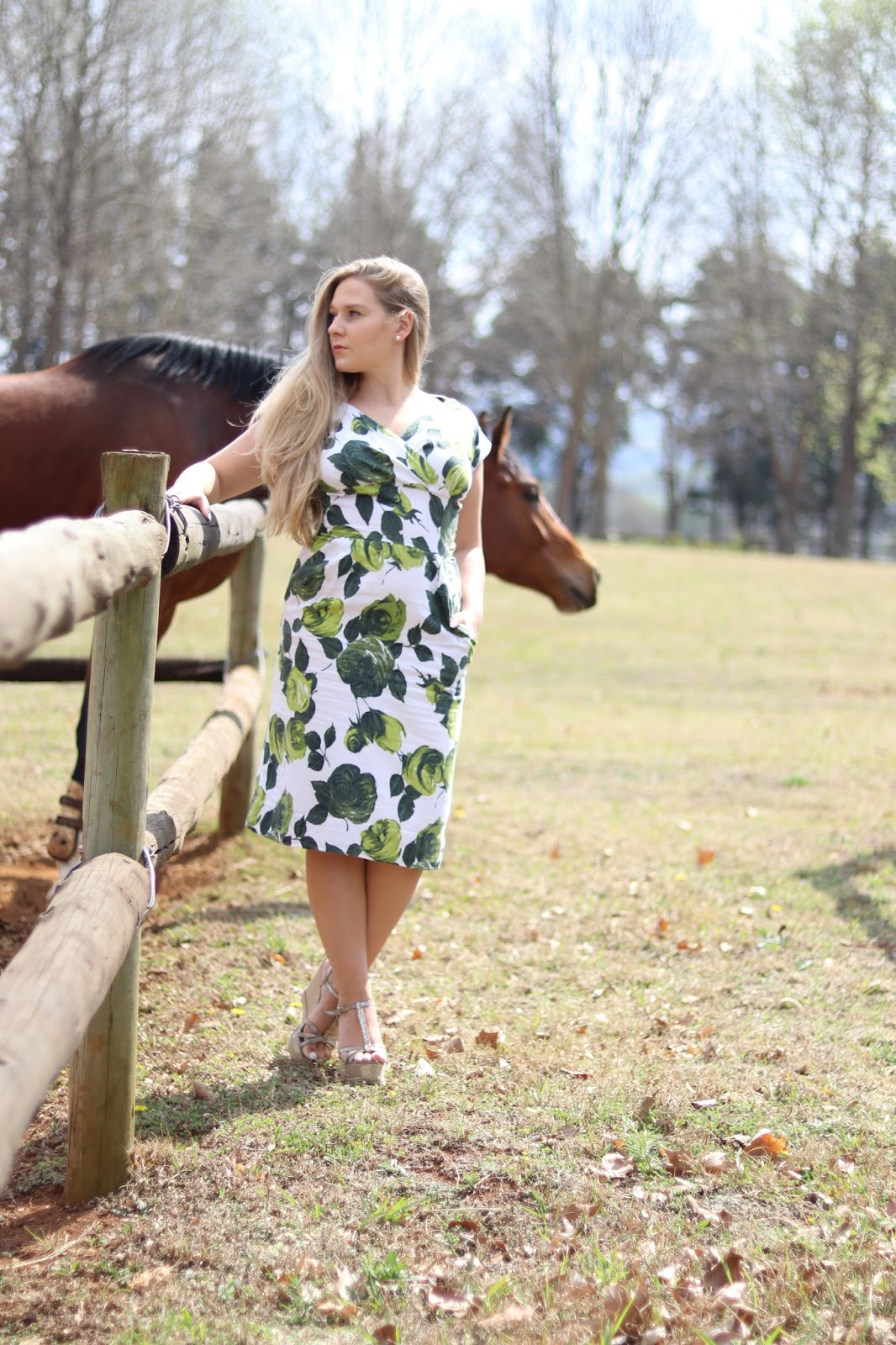 Katie Heath wearing green and white dress with a horse at Ardmore Ceramics, South Africa