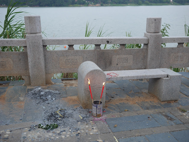 two traditional Chinese red candles burning in a can next to the river