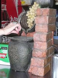 Racimo de uvas y mano depositando una moneda en una especie de pequeña fuente