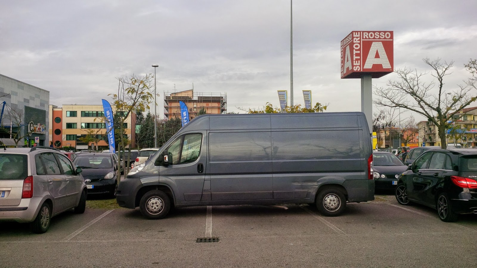 A van is parked across three parking spaces in a car park