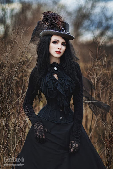 Gothic Victorian Steampunk woman wearing all black (steamgoth) with a gray hat with feather plume.