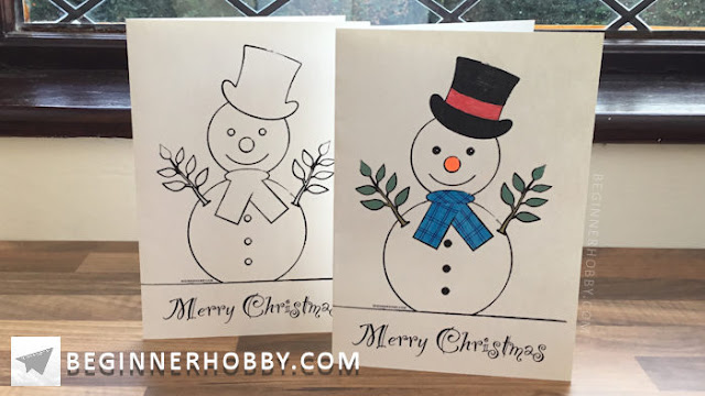 A picture of 2 printed Christmas cards - one is coloured in.