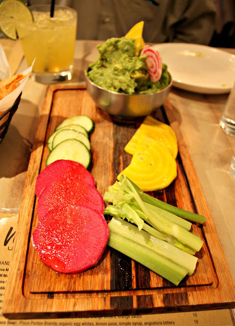 Fresh and healthy guacamole plate at Mesa Urbana featuring vibrant dipping vegetables.