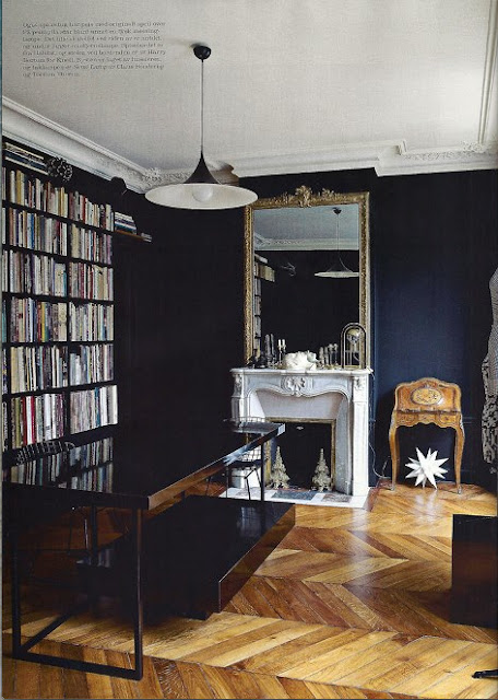 A home library with chevron floors and black wall