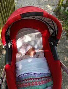baby in stroller sleeping under Crochet baby blanket colorful afghan