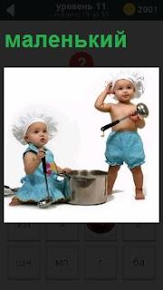 Двое маленьких поварят с половниками и кастрюлей в колпаках пытаются приготовить еду