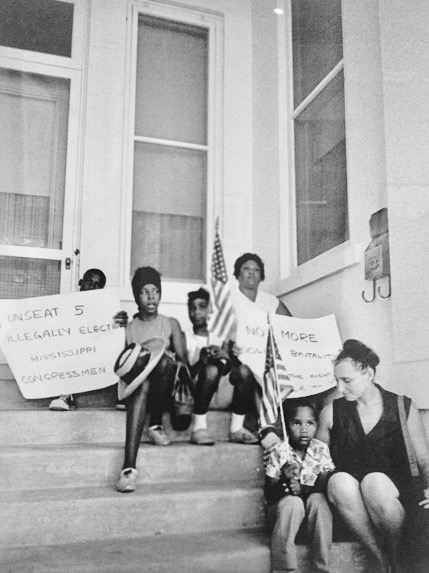 Mrs. Aylene Quinn from McComb and her four children sit on the steps of the Governor's mansion in Jackson, Mississippi. 1965 Photo by Matt Herron