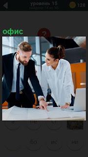 Мужчина и женщина работают с документами в офисе за столом