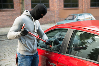man breaking window of vehicle