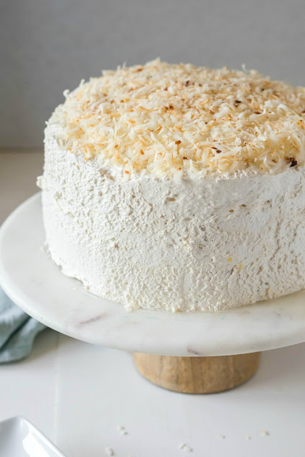 haleakala cake with toasted coconut on top on a marble and wood cake stand
