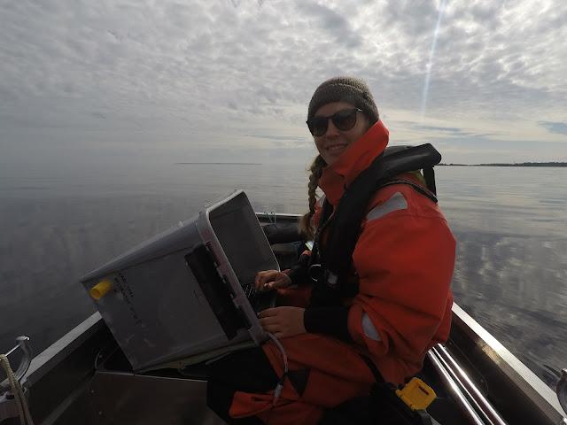 Hymyilevä kartoittaja maastotoimistossa, eli veneessä muovilaatikolla suojattu tietokone sylissä.