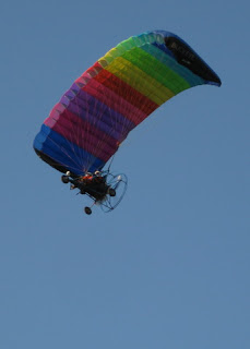 Rainbow powered paraglider overhead, McArthur, CA.