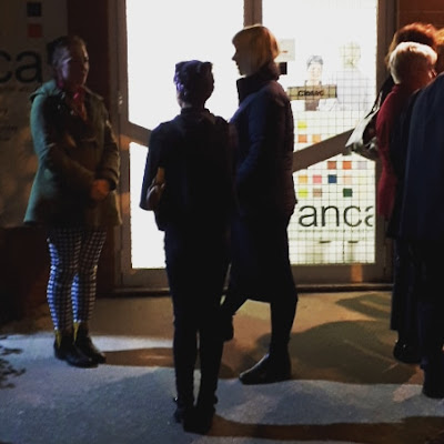 A group of people waiting outside a gallery in the dark. On the gallery door is a sign that reads 'closed'.