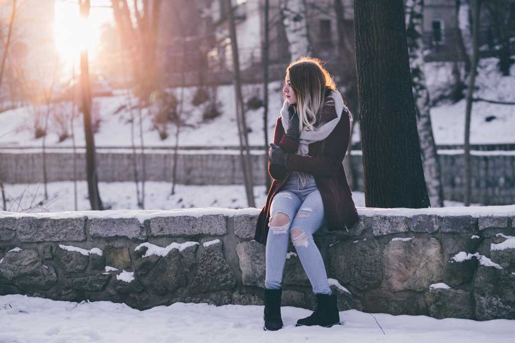 Girl sitting on wall in winter