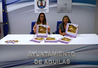 Fotografía del acto celebrado en la sala de prensa del ayuntamiento, la edil y la técnica del centro posando con el cartel de la programación