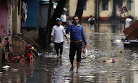 People walk through a partially flooded street Aug. 30 at a residential area in Mumbai, India. (Credit: CNS photo/Danish Siddiqui, Reuters) Click to Enlarge.